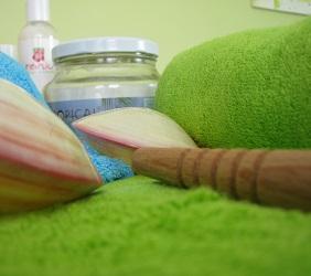 Kompozice ručníku, mušlí, olejů a tyčky na thajskou masáž